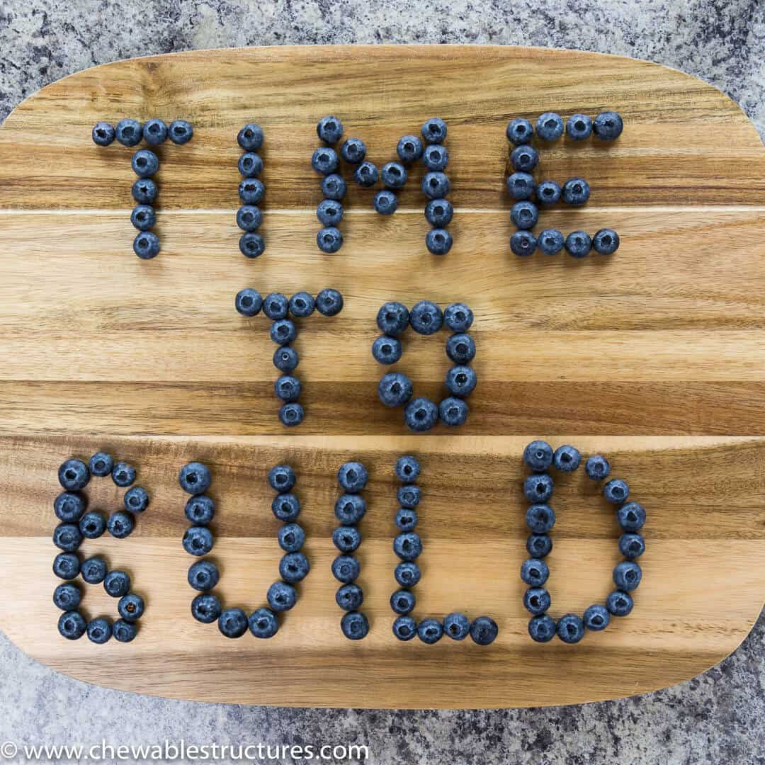 The words Time to Build spelled out using blueberries on a cutting board