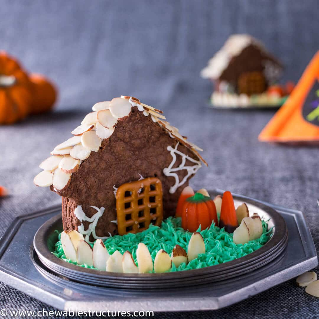 house shaped chocolate brownie topped with shaved almond roof shingles and fence the house are you looking for halloween potluck ideas