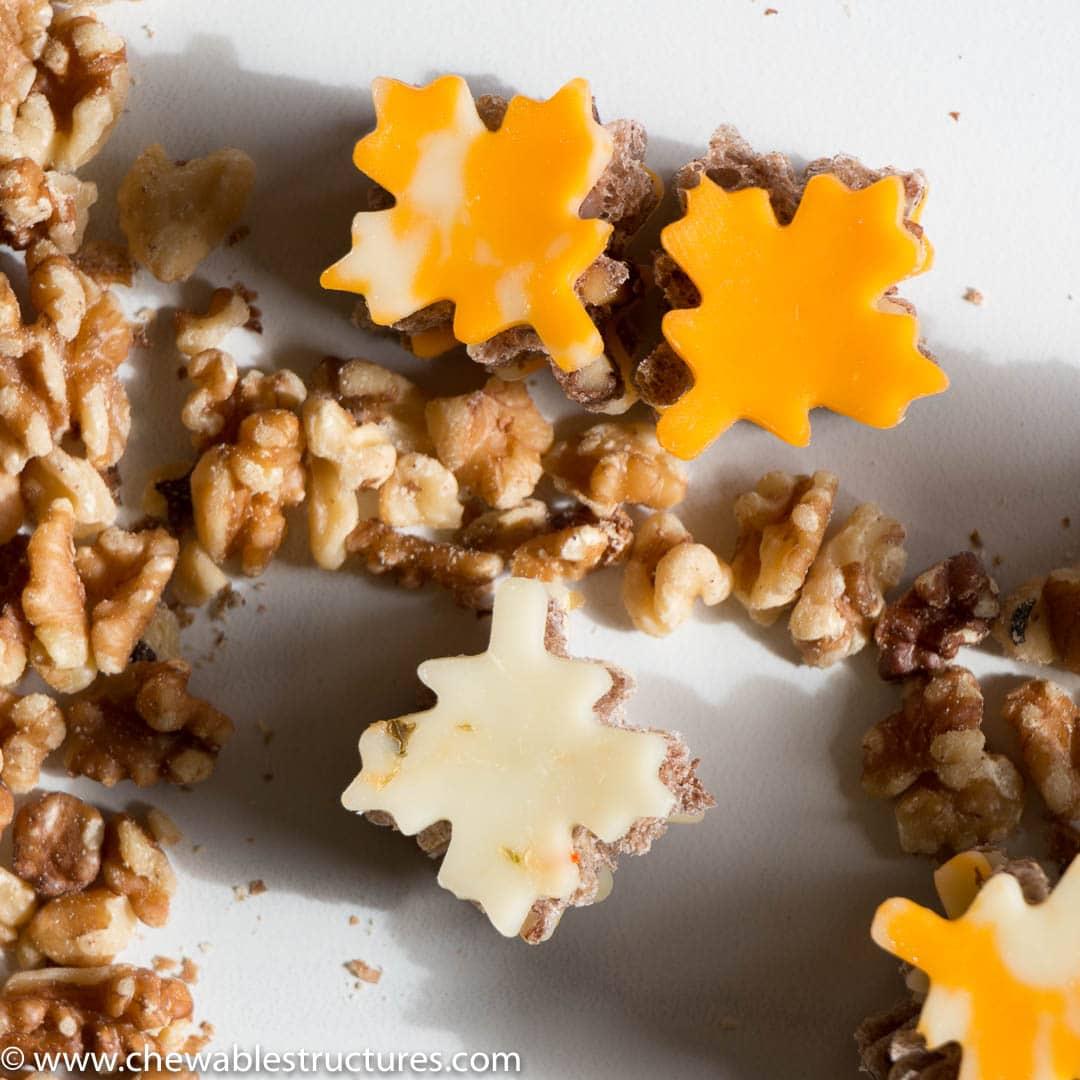 leaf-shaped cheese slices, leaf-shaped walnut bread, and whole walnuts on a cutting board