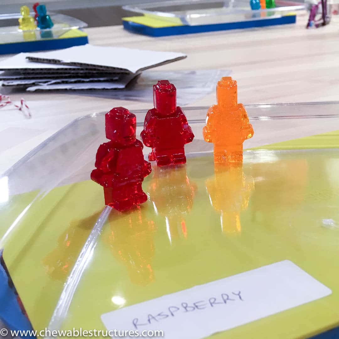 Raspberry and apricto gummy LEGO people are standing on a plate.