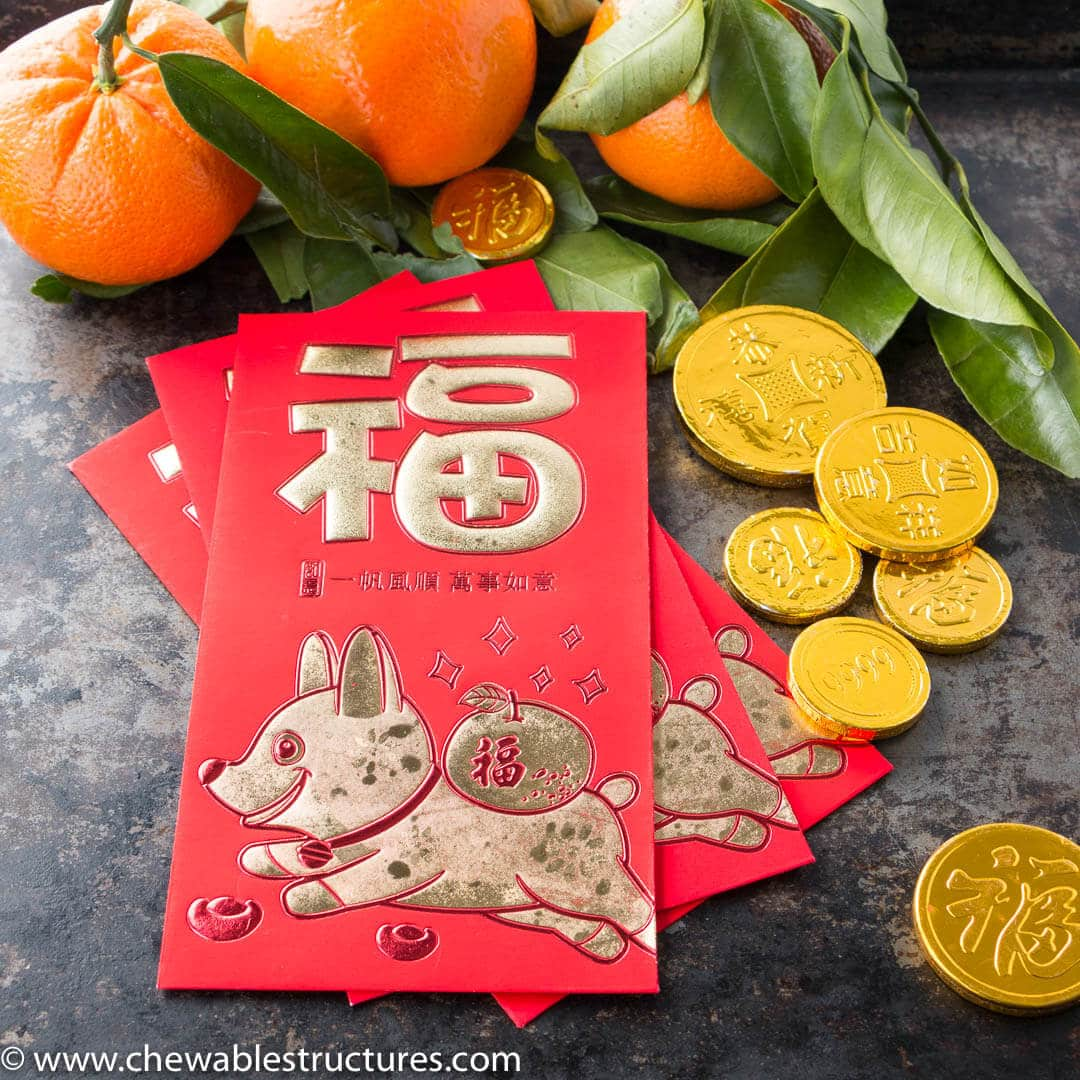 A red envelope (with Chinese characters) next to symbolic mandarin oranges