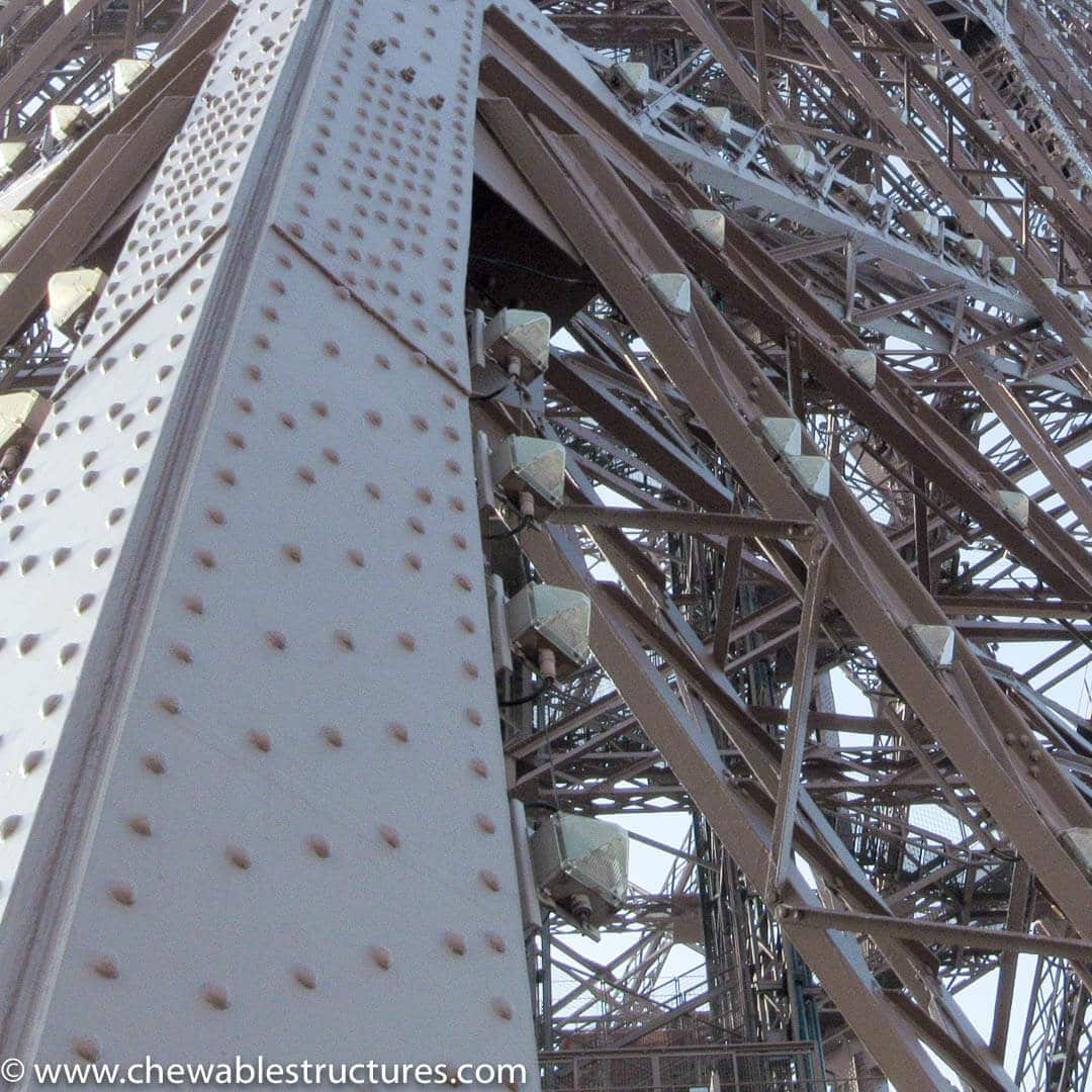 Close up of the iron work of the Eiffel Tower to emphasize how tall is the Eiffel Tower