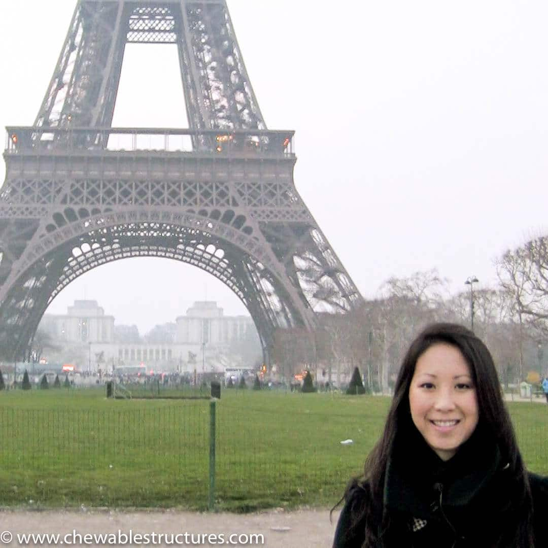 A lady stands in front of the Eiffel tower in Paris, France to show audiences how tall is the Eiffel Tower