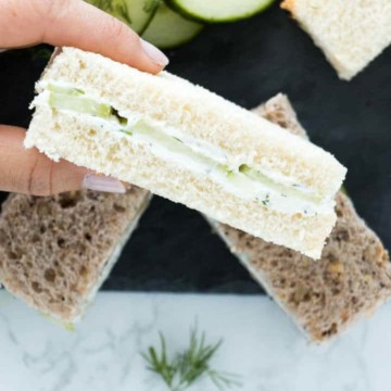 hand holding cucumber sandwich above cucumber slices and more sandwiches