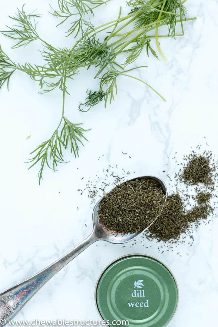 Top view of fresh dill and dried dill on a marble table.
