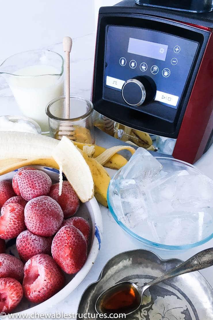 ingredients to make a strawberry banana smoothie is sitting on a table, including: a Vitamix blender A3500, frozen strawberries, fresh banana, skim milk, Greek yogurt (plain), vanilla extra, honey, and ice.