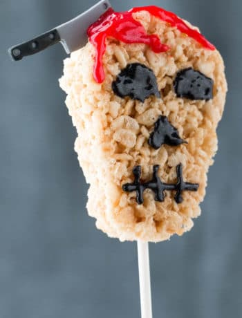Close up showing how to prepare easy Halloween treats for school using rice krispie treats, edible blood and an edible sugar candy cleaver.