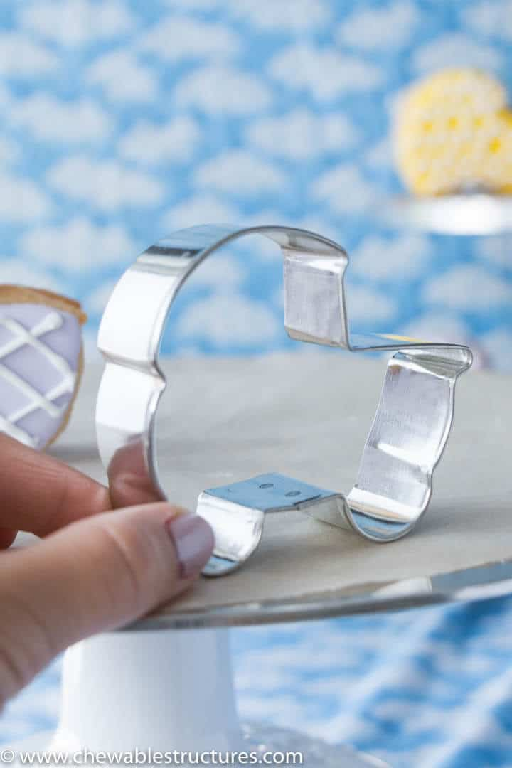 hand holding a baby carriage-shaped cookie cutter