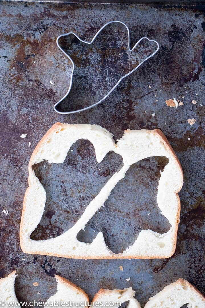 Ghost cookie cutter and a slice of bread on a cookie sheet.