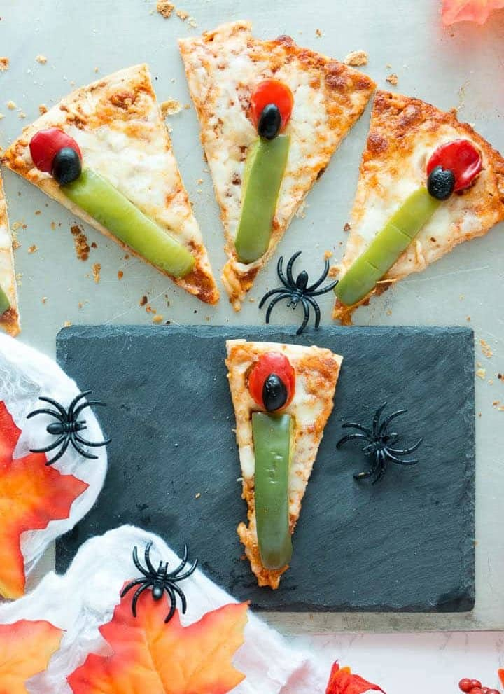 Slices of vegetarian pizza topped with spooky witch fingers made of green peppers, red peppers and black olives.