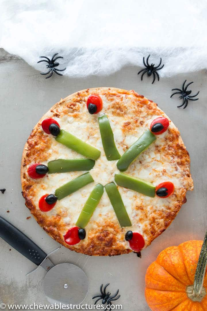 A whole vegetarian pizza on a baking sheet decorated for Halloween with witch fingers made of vegetables.