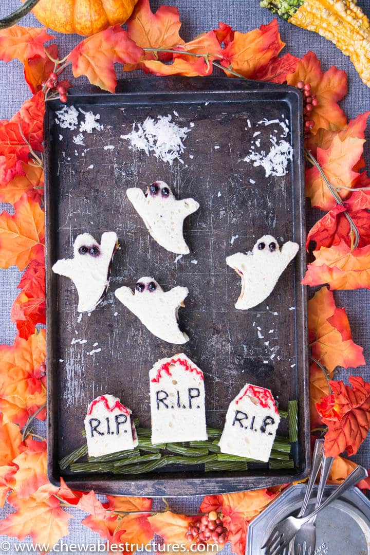 ghost and tombstone-shaped Halloween sandwiches on a baking sheet