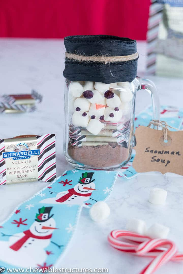snowman soup in a mason jar next to Ghirardelli peppermint bark squares