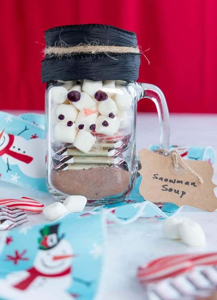 Mason jar decorated as a snowman with hot chocolate mix, candy cane, marshmallows and Ghirardelli peppermint bark squares inside.