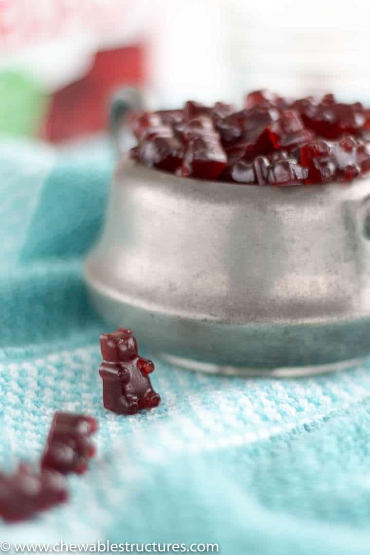 homemade gummy bears piled up inside a grey cup alongisde gummy bears on a tea towel