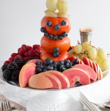 Snowman made of Fuyu persimmons, blueberries, and green grapes.