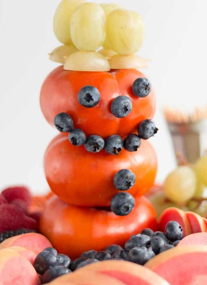 snowman made of persimmon, blueberries, green grapes