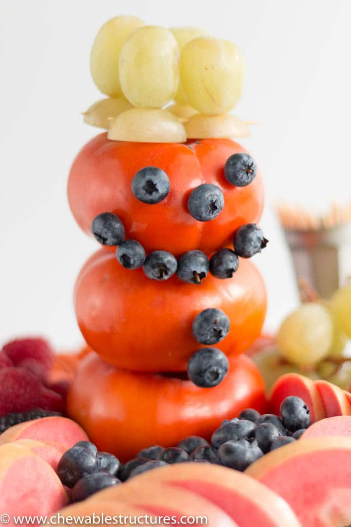 snowman made of 3 fuyu persimmons, blueberries and green grapes