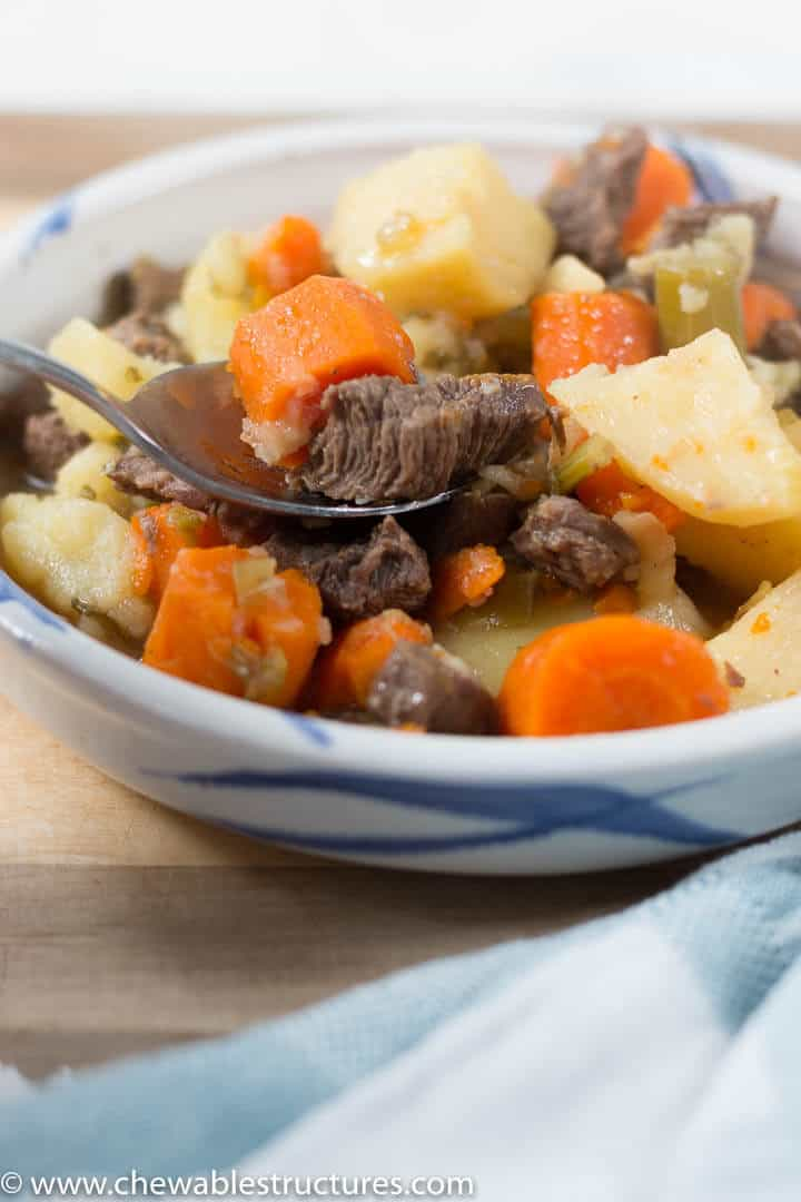 a spoon filled with instant pot beef stew in a shallow bowl