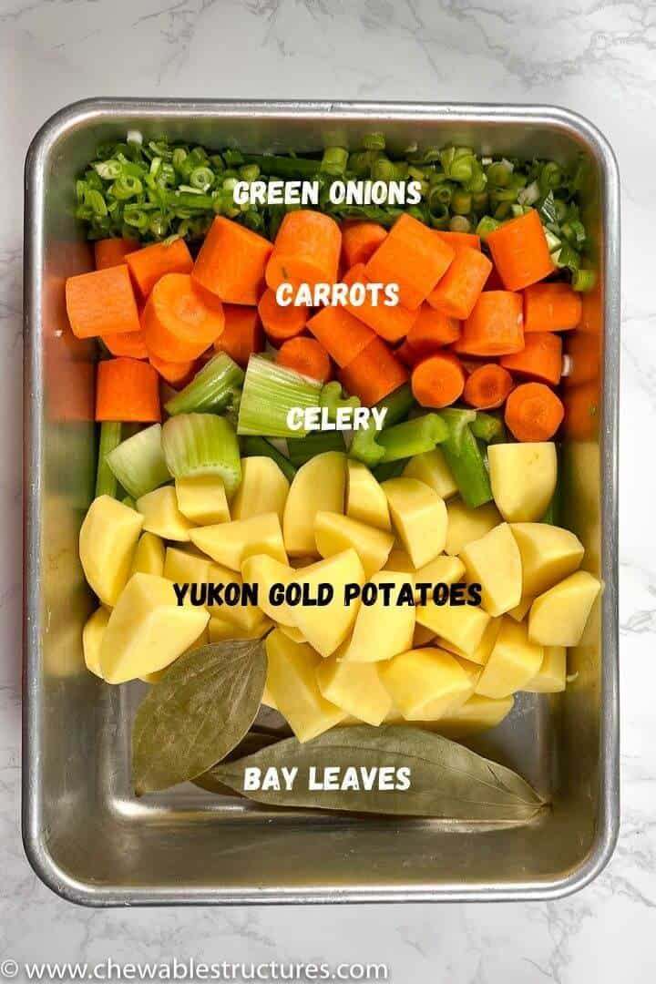 green onions, carrots, celery, potatoes, and bay leaves in a tray