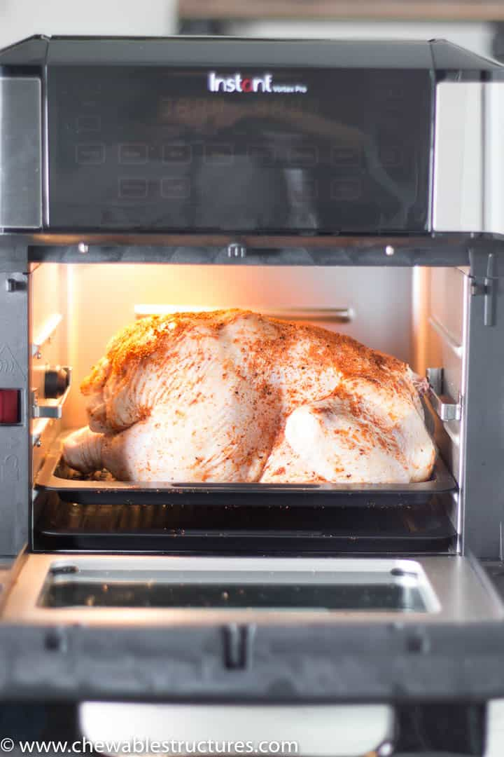 Uncooked, seasoned whole chicken in the Instant Vortex Pro Air Fryer Oven