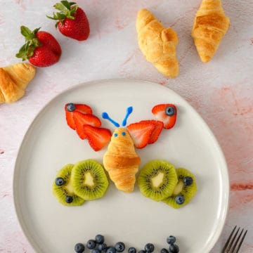 butterfly made of a mini croissant, strawberries, kiwis and blueberries on a plate