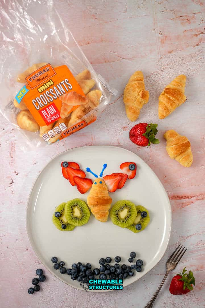 edible butterfly made of croissant and fresh fruit on a plate next to Thomas' mini croissant package