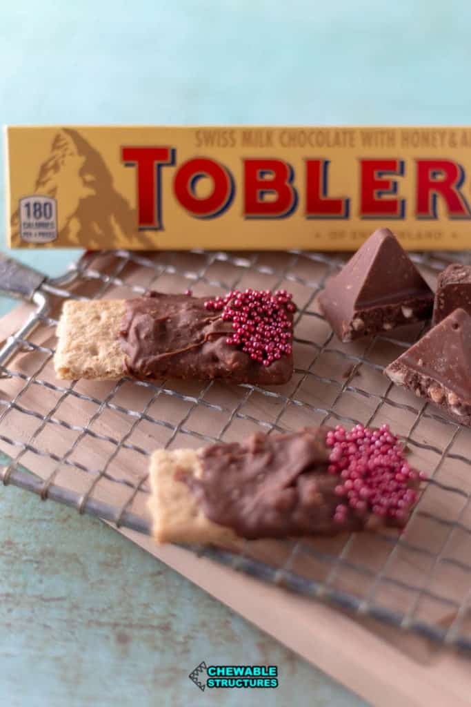 graham crackers covered in melted Toblerone chocolate topped with sprinkles on a serving board