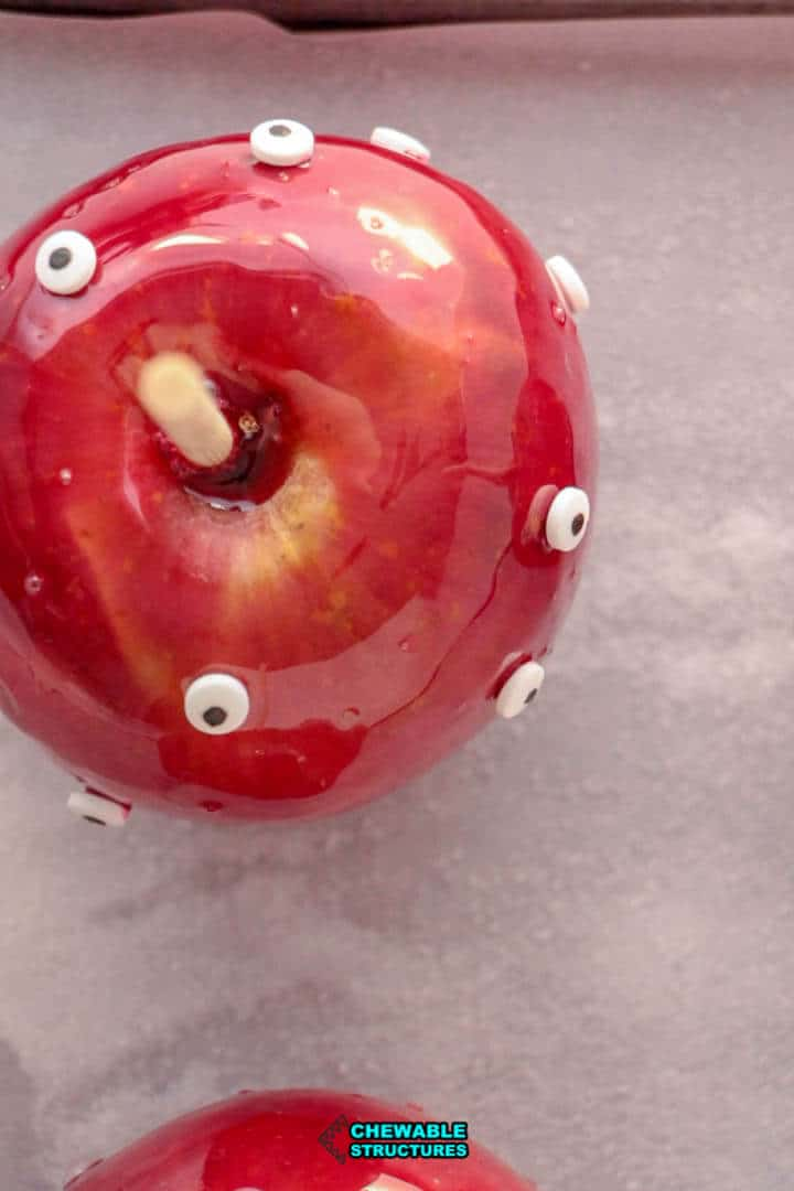 candy googly eyes stuck to the outside of a Halloween candy apple